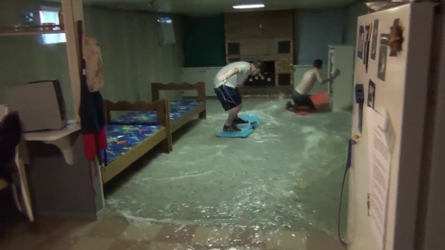 Guys playing on sleds in flooded basement