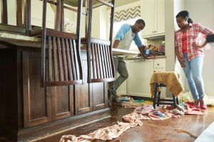 two homeowners assess water damage on wood floor