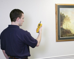 Man holding a device to the wall