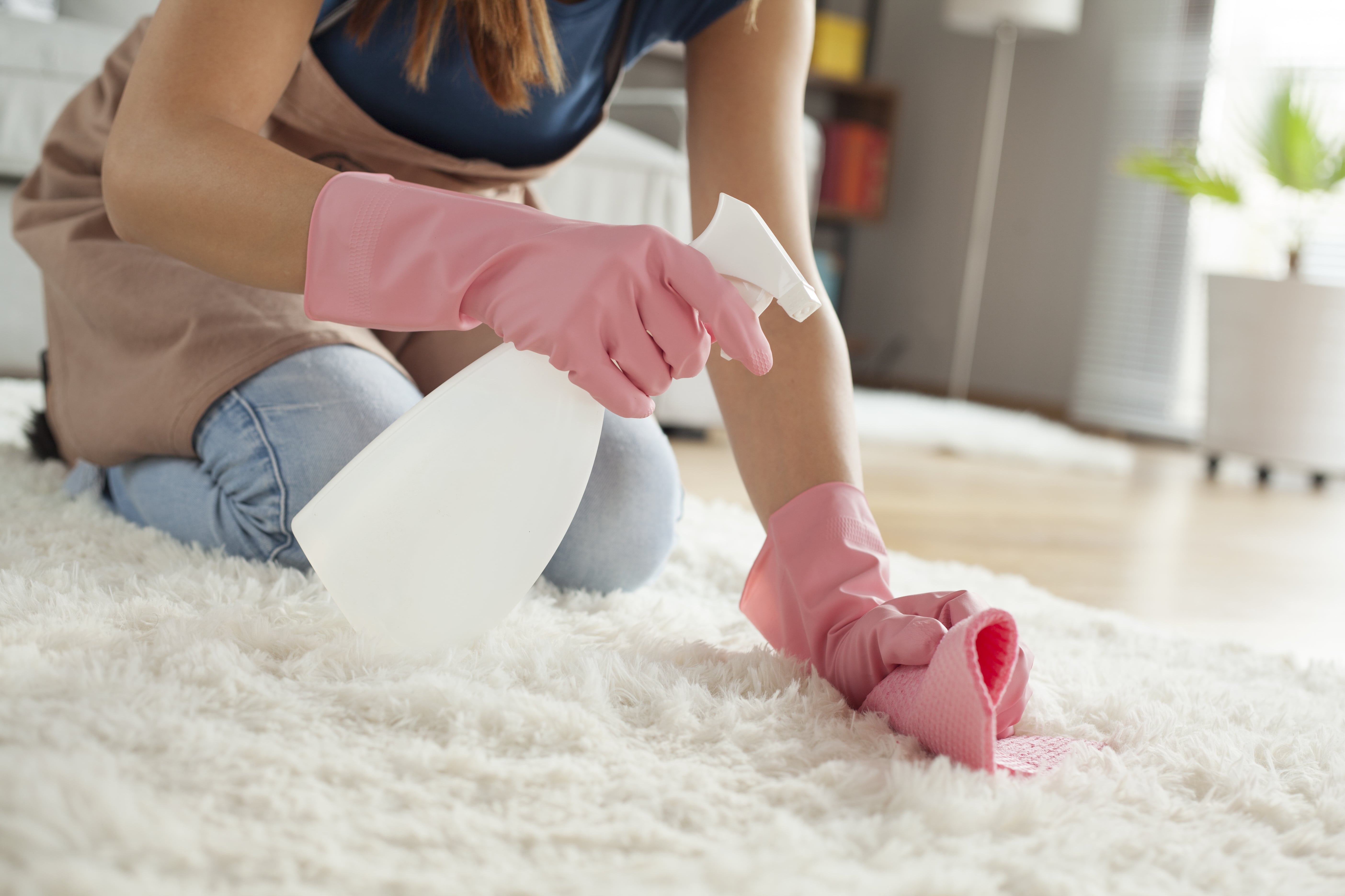 woman wearing pink cleaning gloves using mixed solution to blot out carpet stain