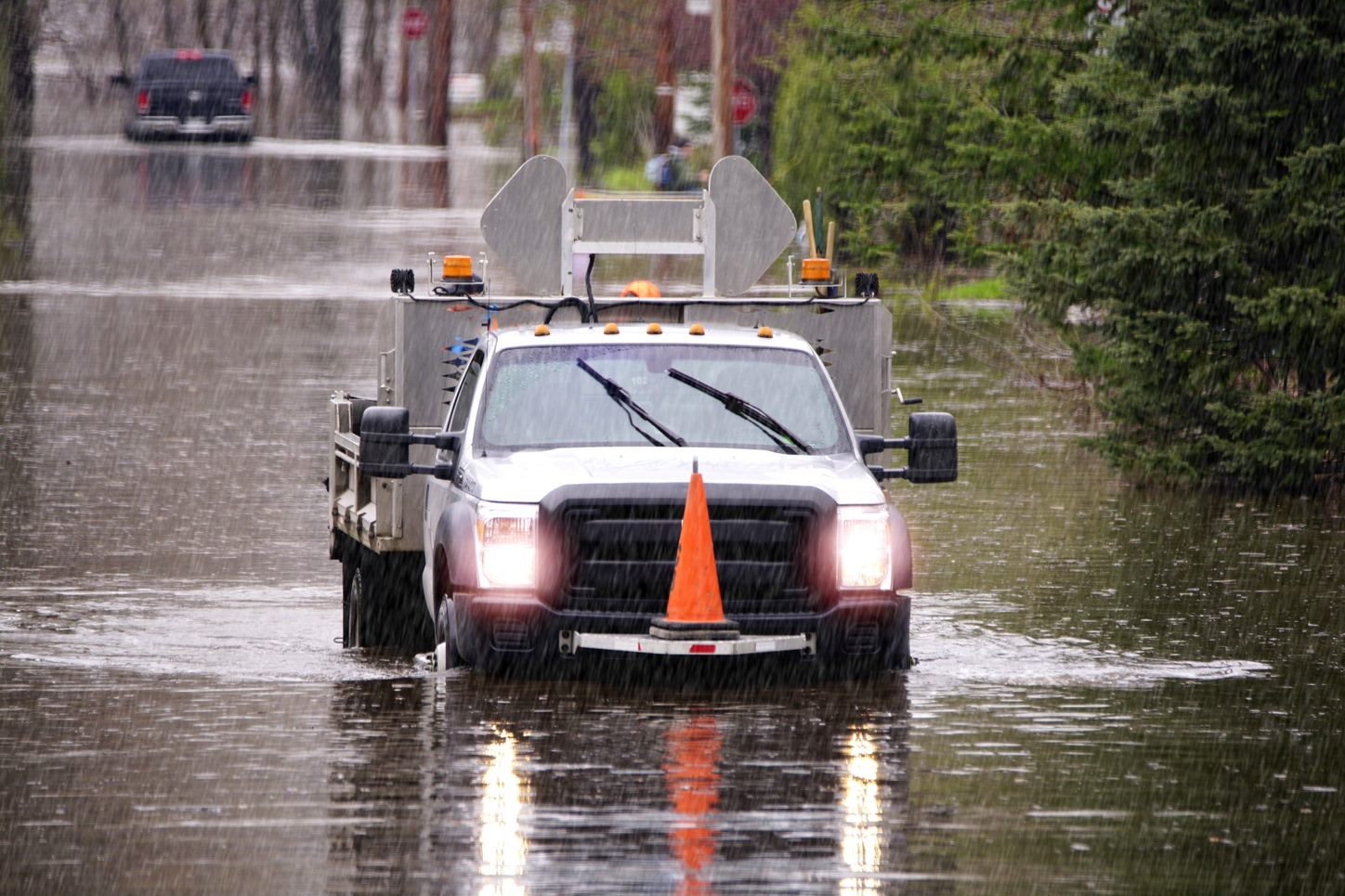 A truck is driving through rain and a flooded street
