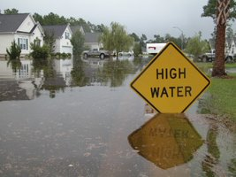 Flood in neighborhood with a sign saying High Water