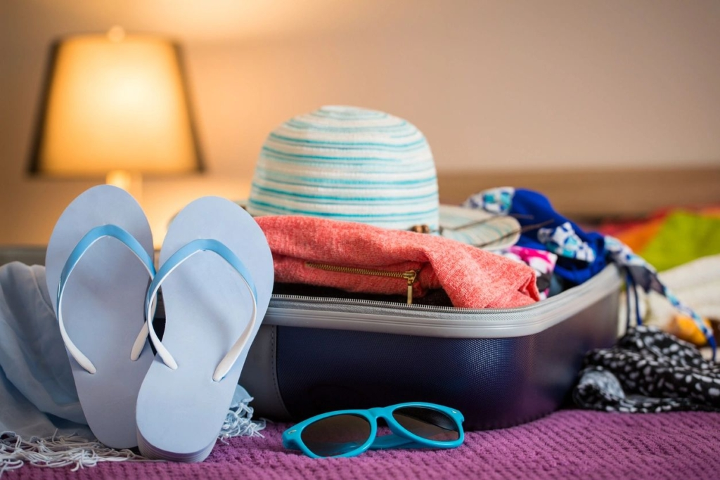 Pool accessories in a suitcase siting on a bed
