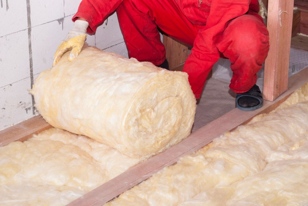 A person laying down insulation