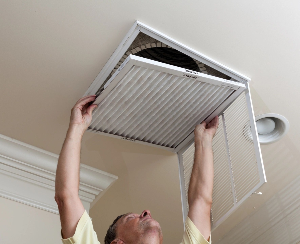 Man replacing an air vent filter