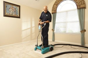 Man cleaning a floor on a cleaning device