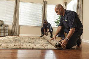 Two men rolling up a carpet
