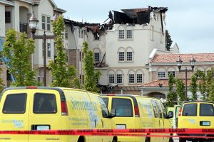 Commercial  building destroyed and yellow trucks driving towards it