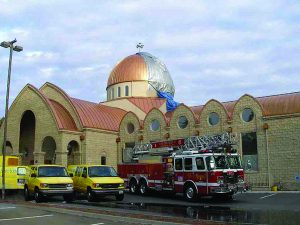 Church being restored with a firetruck in front and yellow trucks