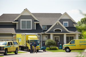 Servicemaster trucks in front of a home