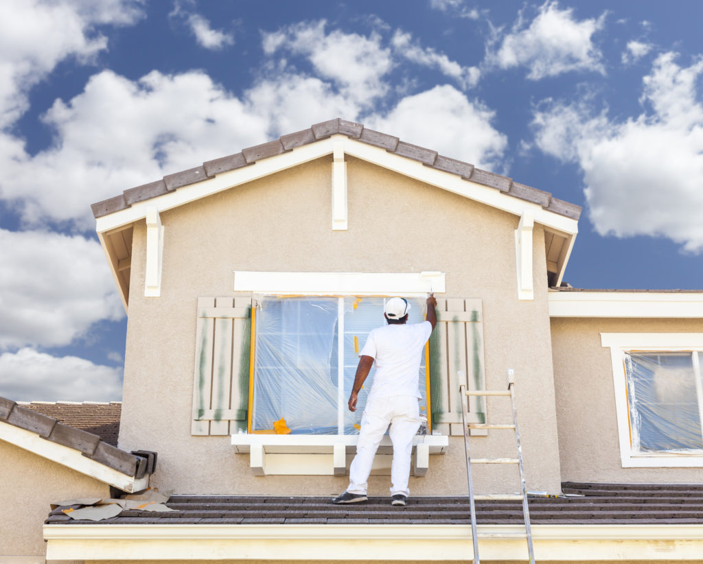 Man paiting exterior of a house
