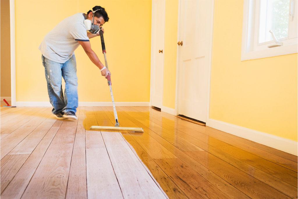 man staining wood floor