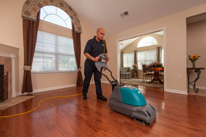 Man cleaning a wood floor.
