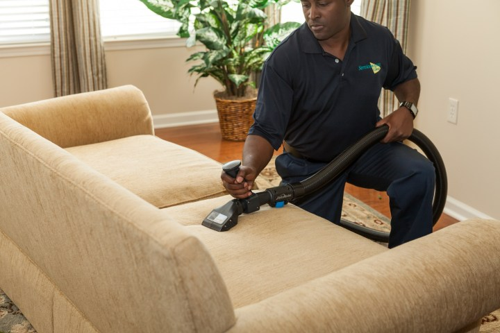 Man cleaning a sofa