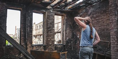 Woman standing in a burned down home