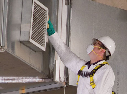 Man in a uniform checking a vent