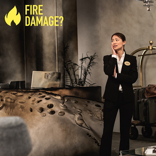 Woman standing in a burned down lobby: Fire Damage?