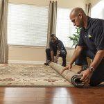 two men rolling up carpet