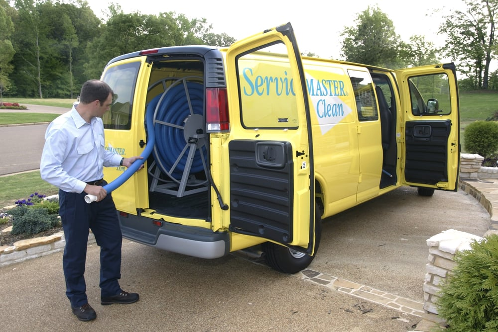 ServiceMaster technician taking a hose out of company van for sewage cleanup