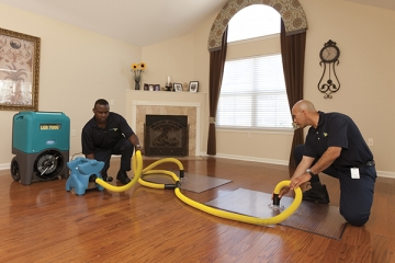 Two men cleaning a floor