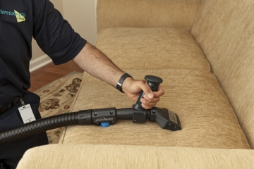 person cleaning a couch with a vacuum