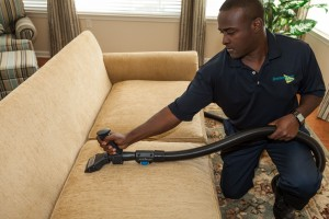 man cleaning couch cushions