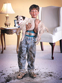 Boy holding messy dog over clean carpet