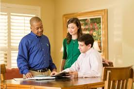 A ServiceMaster technician reviewing a mold removal service with two customers in their home