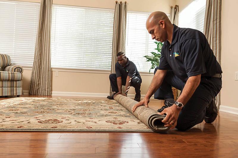 Two men rolling a carpet