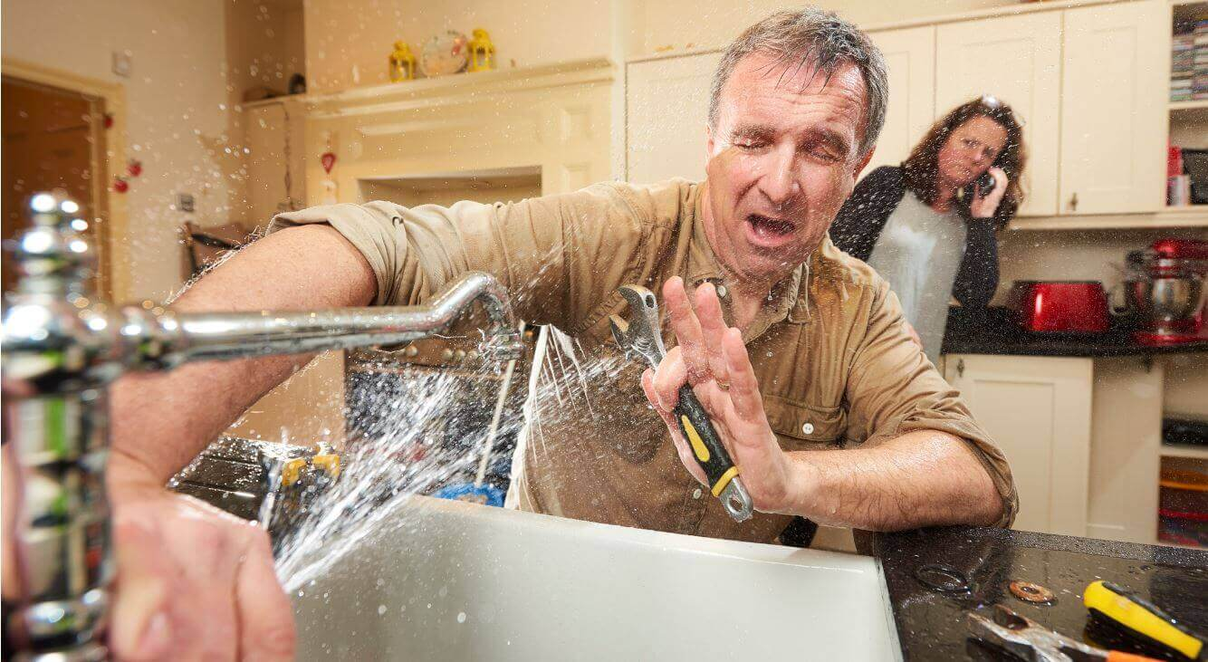 Man Trying to Fix Busted Kitchen Pipe