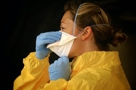 Woman Wearing Gloves, Body Protectant, and Adjusting Face Mask