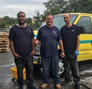 Three men standing in front of a van smiling