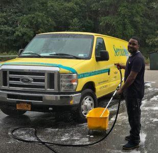man washing a yellow van