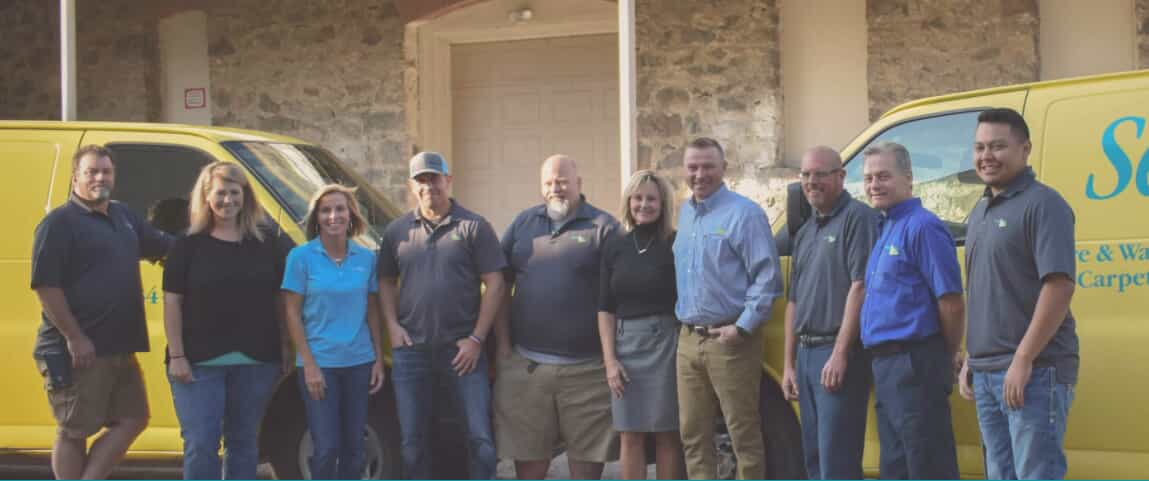 Staff photo of smiling people infront of a home