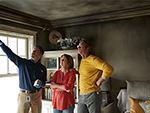 Three people standing in a burned down room