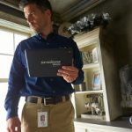 Man holding a ServiceMaster tablet