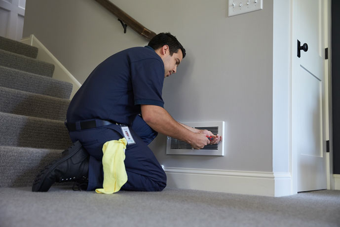 A ServiceMaster technician replacing a vent in a home after mold restoration was completed