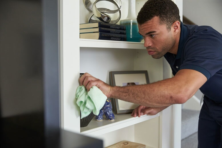 A ServiceMaster technician wiping down a bookcase