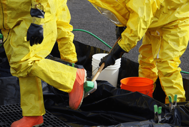 Two technicians in biohazard suits following biohazard cleanup best practices