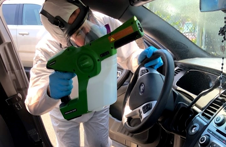 Person disinfecting a car